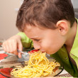 Kid eating pasta - Stock Photo