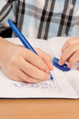 Anonymous pupil hand writing homework — Stock Photo