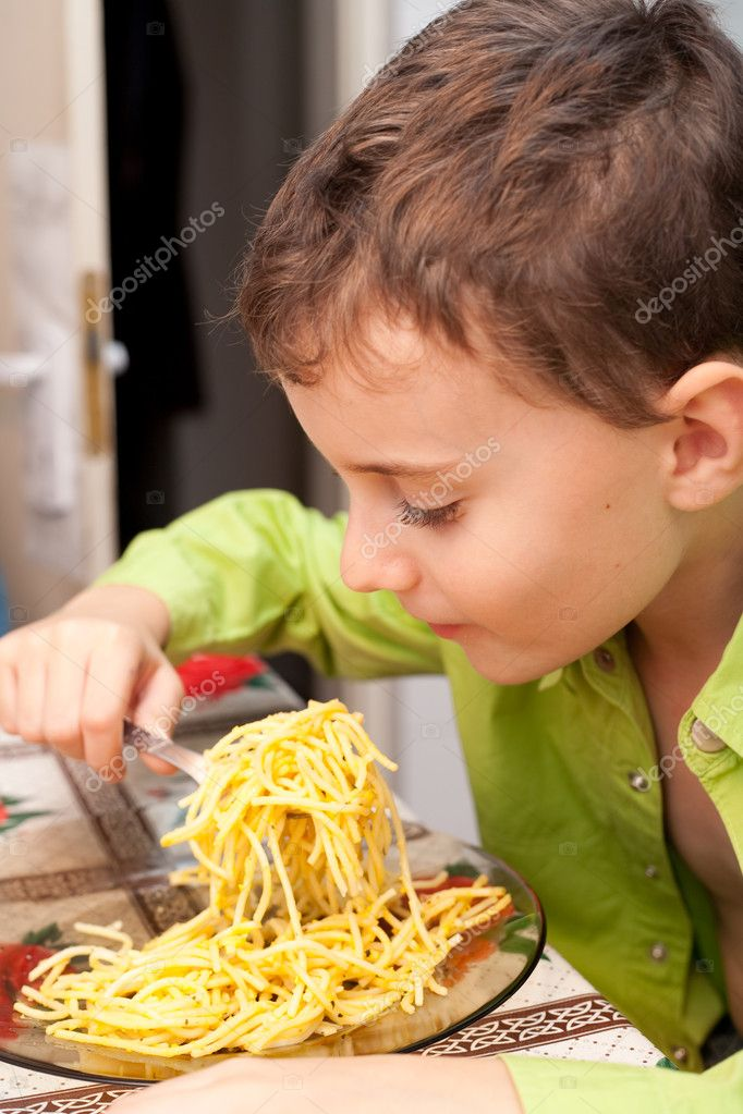 Cute kid eating delicious pasta, indoor shot — Stock Photo #2006975