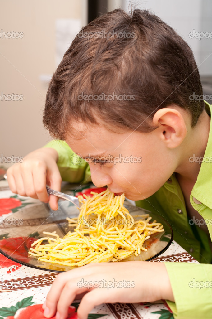 Cute kid eating delicious pasta, indoor shot — Stock Photo #2006980