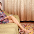 Young lady sitting on sofa — Stock Photo