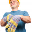 Blue collar worker putting on gloves - Stock Photo