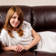 Beautiful blonde on a leather couch — Stock Photo