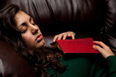 Young lady sleeping on sofa with a book — Stok fotoğraf
