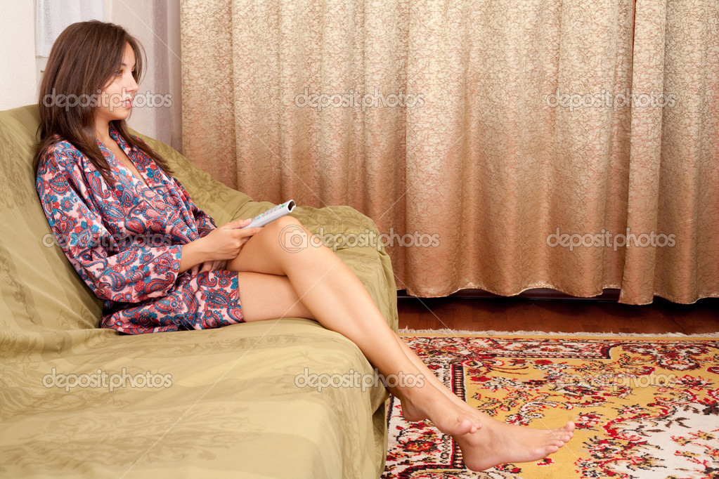Young lady with remote control in her hand sitting on sofa, watching tv  Stock Photo #2010022