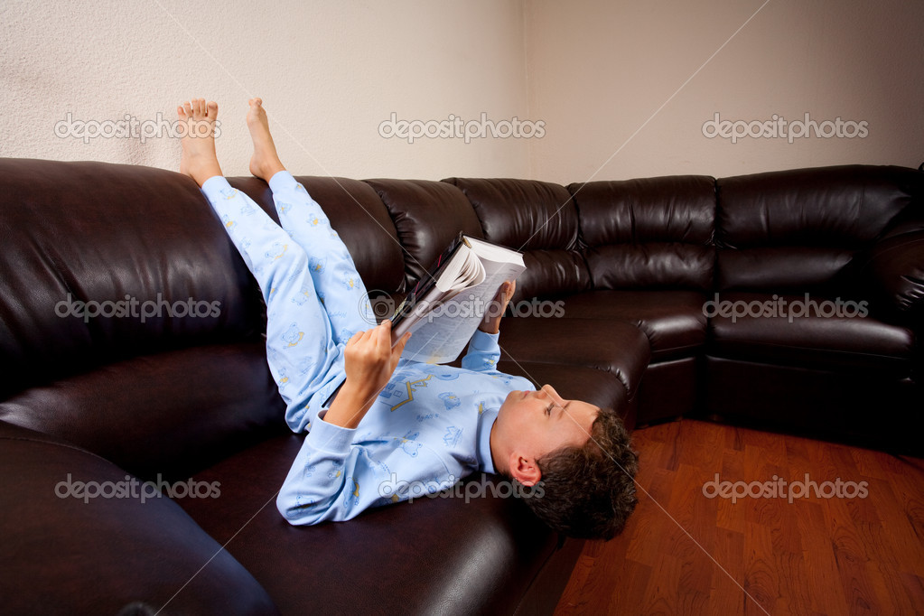 Cute schoolboy in pajamas reading a book (a dictionary) while sitting on a sofa upside down — Stock Photo #2011755
