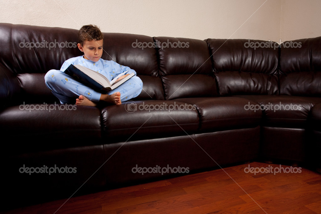 Cute schoolboy in pajamas reading a book while sitting on a leather sofa — Stock Photo #2011776