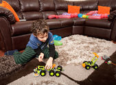 Child playing with plastic trucks — Stock Photo