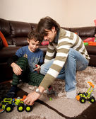 Brothers playing with plastic trucks — Stock Photo
