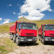 Two large red dump trucks — Stock Photo
