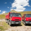 Two large red dump trucks - Stock Photo