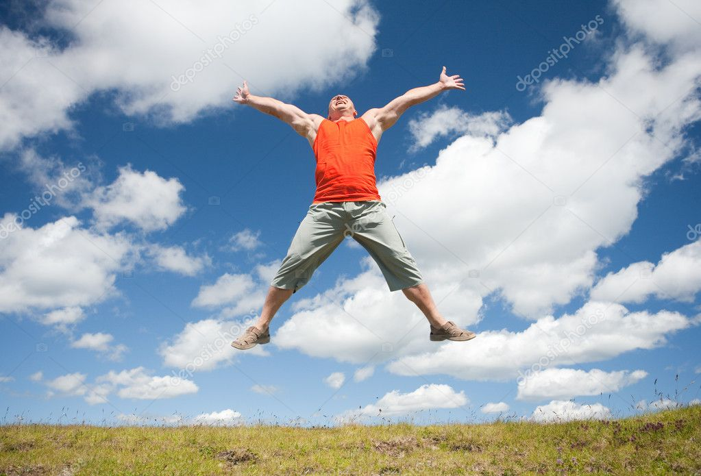 Young man jumping for joy in a beautiful landscape with blue sky and clouds — Stock Photo #2209879