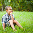 Cute kid sitting in grass — Stock Photo