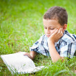 Cute kid reading a book outdoor — Stock Photo #2210145