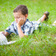 Cute kid reading a book outdoor — Stock Photo