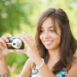 Young lady taking photos outdoors - Stock Photo