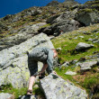 Boy climbing mountain - Stock Photo