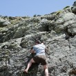 Strong man climbing mountain - Stock Photo