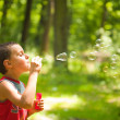 Cute kid blowing soap bubbles — Stock Photo