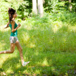 Beautiful girl running through forest — Foto de Stock