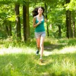 Beautiful girl running through forest — Stock Photo