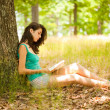 Royalty-Free Stock Photo: Brunette girl reading a book outdoors