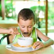 Cute kid eating soup - Stock Photo