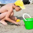 Boy playing in the sand - Stock Photo