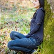 Beautiful girl near a tree trunk — Stock Photo