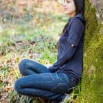 menina bonita perto de um tronco de árvore — Foto Stock