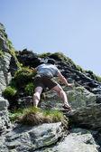 Strong man climbing mountain — Stock Photo