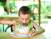 Cute kid eating soup — Stockfoto