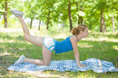 Sporty blonde girl doing fitness outdoor — Stock Photo
