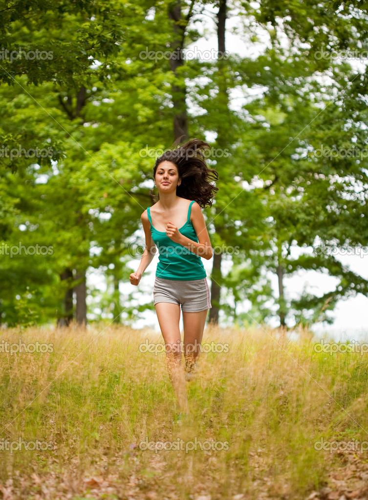 beautiful girl running through forest stock photo