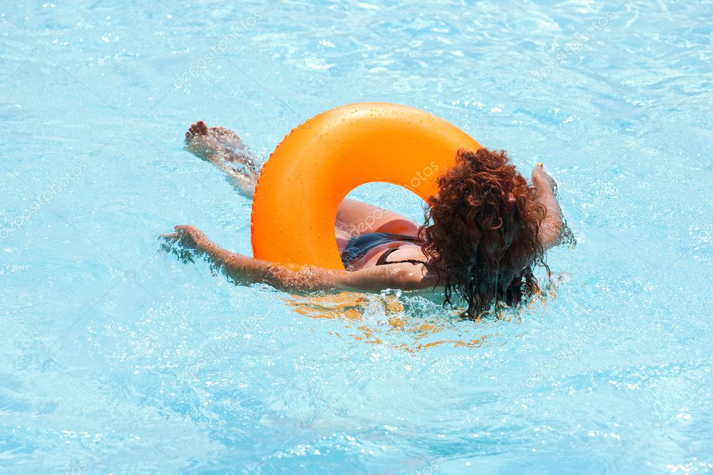 Woman swimming with a rubber ring in a hotel pool — Stock Photo #2213374