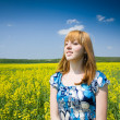 Stock Photo: Blonde in a rape field