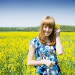 Blonde in a rape field — Stock Photo