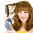 Blonde girl using hair drier — Stock Photo