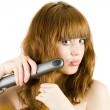 Blonde using hair straightener — Stock Photo #2244434