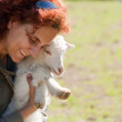 Woman and cute baby goat — Stock Photo