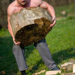 Strong man lifting log - Stock Photo