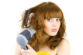Blonde girl using hair drier — Stock Photo