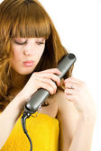 Blonde using hair straightener — Stock Photo