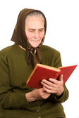 Old peasant woman reading — Stock Photo
