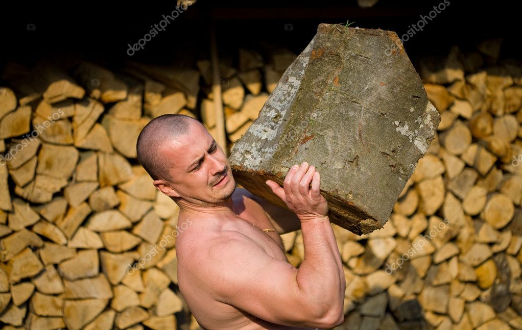 Strong man lifting a huge log, outdoor scene — Stock Photo #2243564