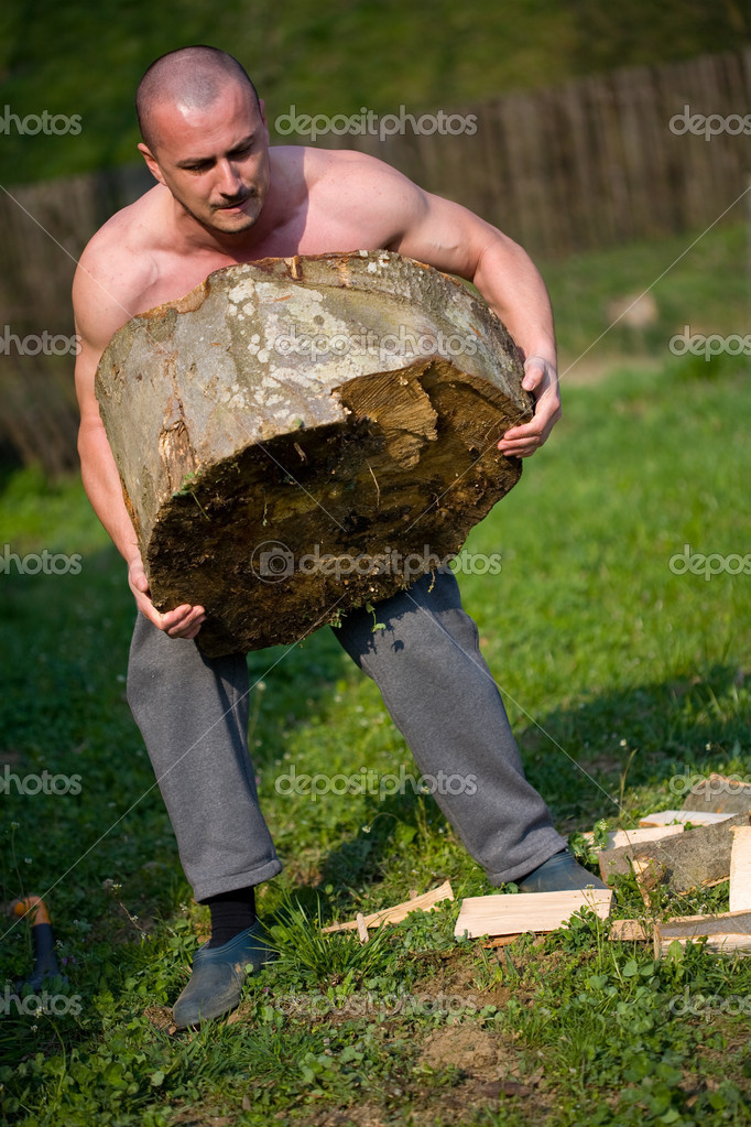 Strong man lifting a huge log, outdoor scene — Stockfoto #2247498