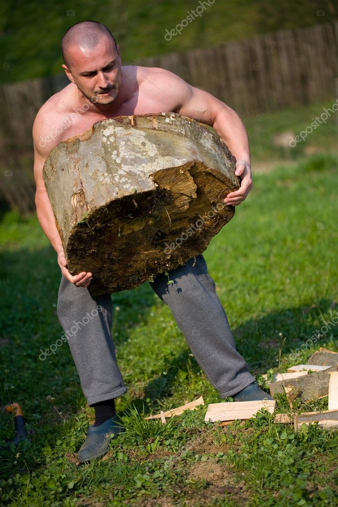 Strong man lifting a huge log, outdoor scene — Zdjęcie stockowe #2247498