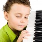 Cute kid playing piano — Stock Photo