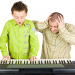 图库照片: Kid playing piano badly