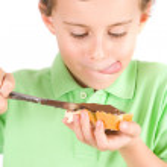 Boy spreading peanuts butter on bread — Stock Photo #2250774